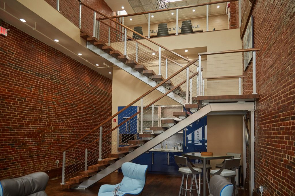 Switchback Floating Stairs with Cable Railing featuring Walnut Treads and Handrail