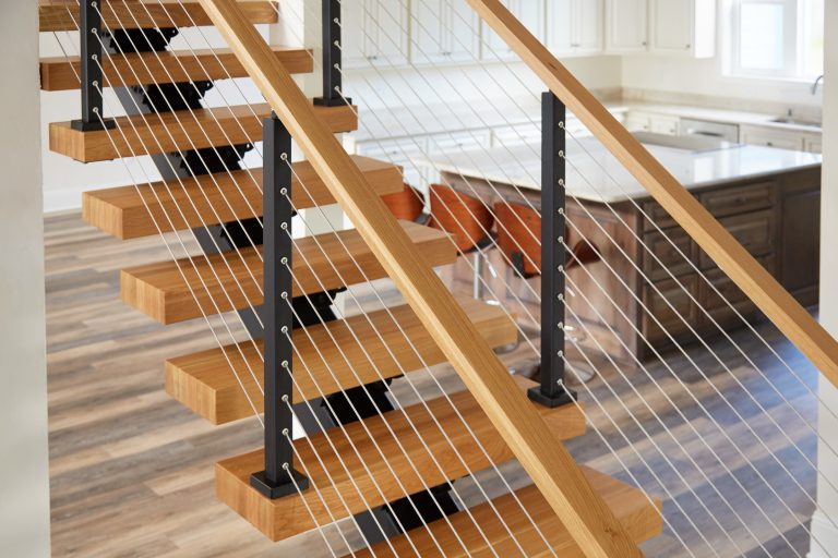 Cable Railing on Floating Stairs featuring White Oak Handrail & Black Powder Coated Posts