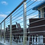 Stainless steel rod railing on an outdoor eating area with patio furniture overlooking the water