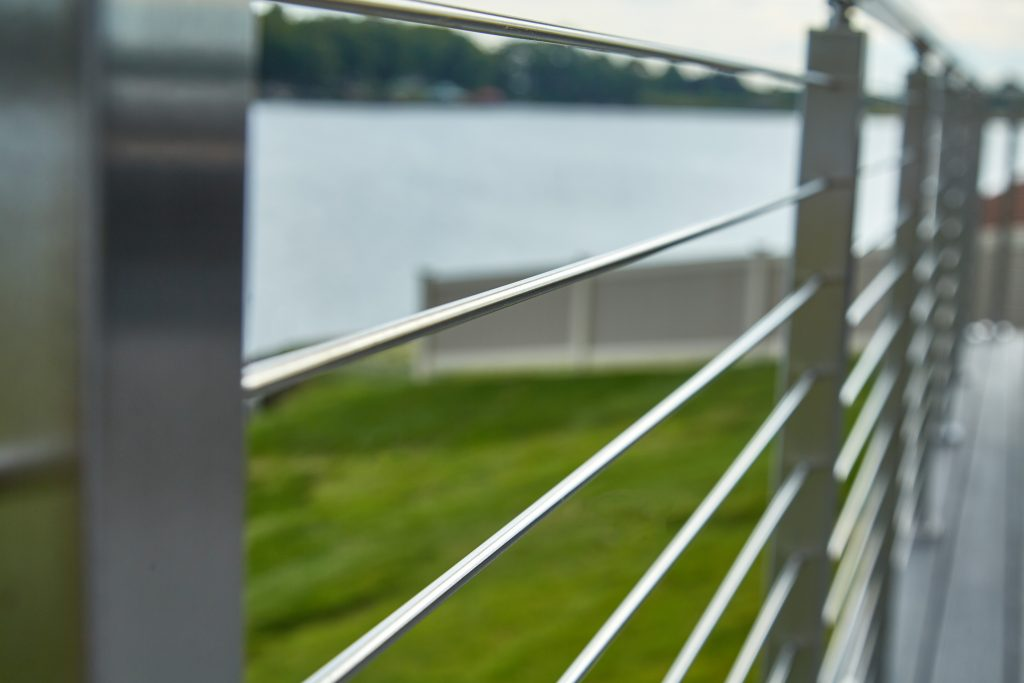 Up close picture of rod railing rods on a deck near the water with grass in the background