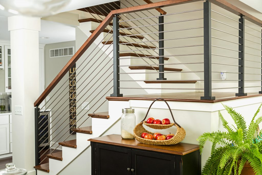 Rod railing system with black powdercoated posts and wooden handrail on a modern farmhouse kitchen staircase