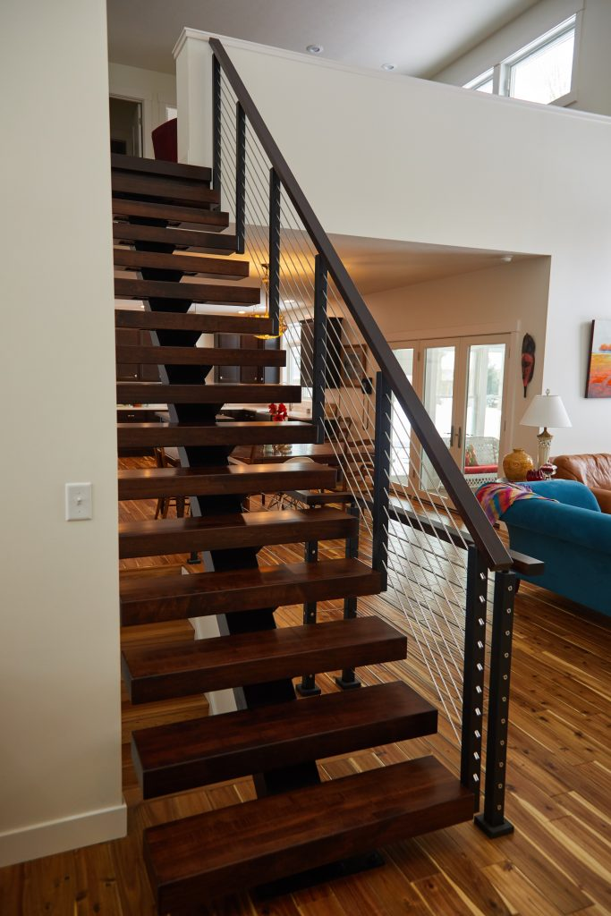 Floating stair system featuring stained hard maple treads & handrail, and rod railing, seen from the front.
