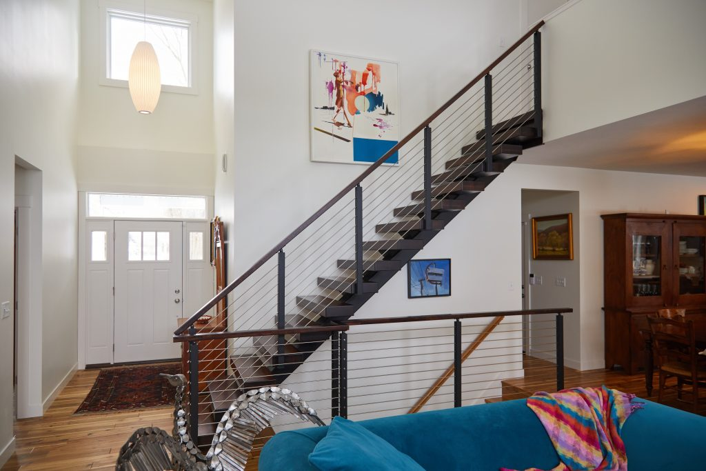 Side view of floating stairs and rod railing guard rail.