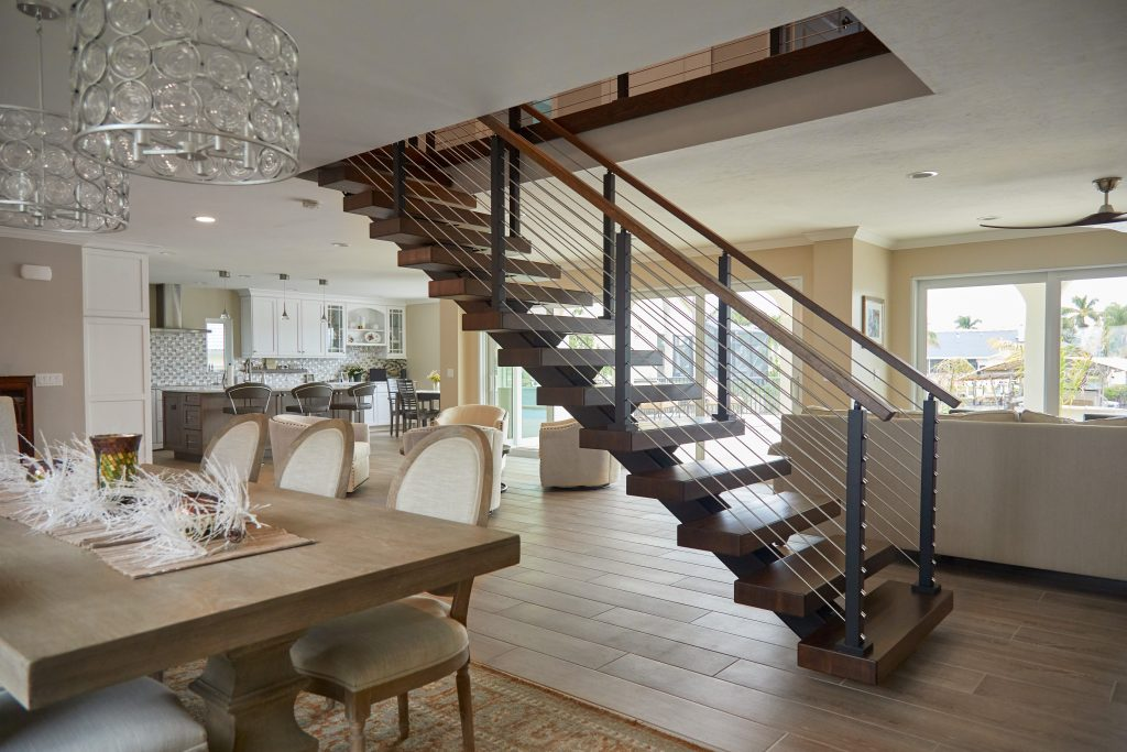 straight stairs in an open concept home feature white oak treads and rod railing.